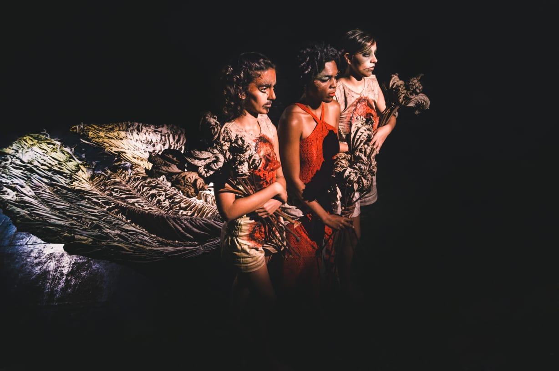 Imagem colorida de palco escuro, com três mulheres com rosto maquiado e roupas em tons avernelhados